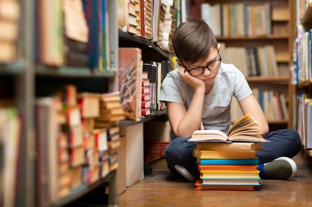 Wysokiego kąta chłopiec przy bibliotecznym czytaniem
