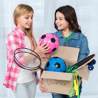 Wysokiego kąta dziewczyny mienia darowizny pudełko