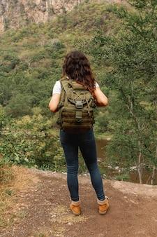 Wysokiego kąta kobieta z plecakiem przygotowywającym badać