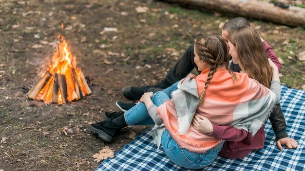 Wysokiego kąta kobiety siedzi przy ogniskiem