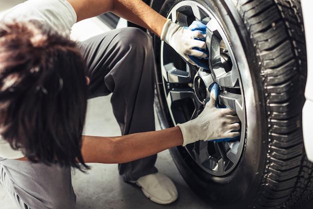 Wysokiego kąta męski mechanik sprawdza samochodowego koło