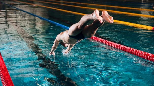 Wysokiego kąta męski pływak nurkuje w basenie
