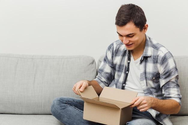 Wysokiego kąta mężczyzna na kanapy otwarcia pudełku