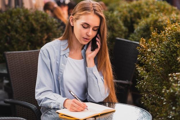 Wysokiego kąta młoda kobieta opowiada nad telefonem