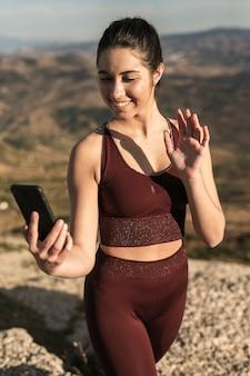 Wysokiego kąta młoda kobieta opowiada rozmowę wideo przez telefonu