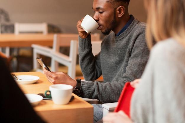 Wysokiego kąta młodzi przyjaciele pije kawę