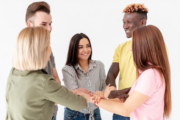 Wysokiego kąta młodzi przyjaciele tworzy kształt z rękami