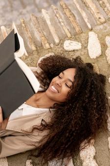 Wysokiego kąta piękna kobieta czyta outside