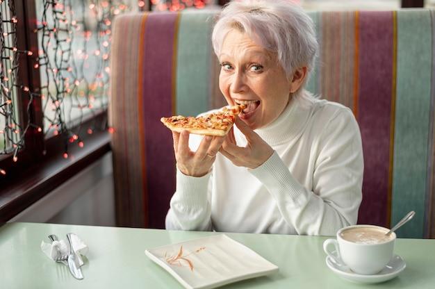 Wysokiego kąta starsza kobieta przy restauracyjnym łasowaniem