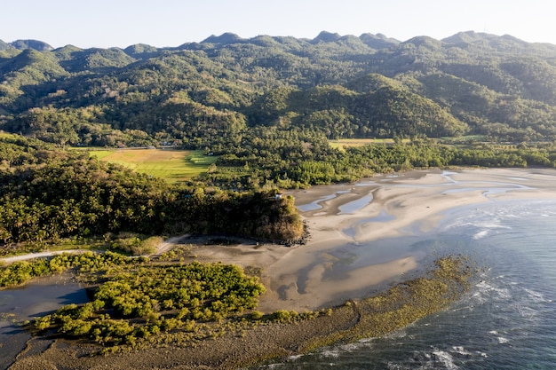 Wysokiego kąta strzał morze blisko brzeg i gór zakrywających w drzewach przy dniem