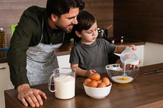 Wysokiego kąta syn i ojciec robi ciastu