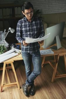 Wysokiego kąta widok azjatycka mężczyzna pozycja przy stołem egzamininuje projekty