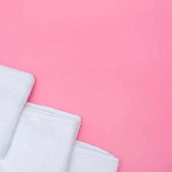 Wysokiego kąta widok biali ręczniki na różowym tle