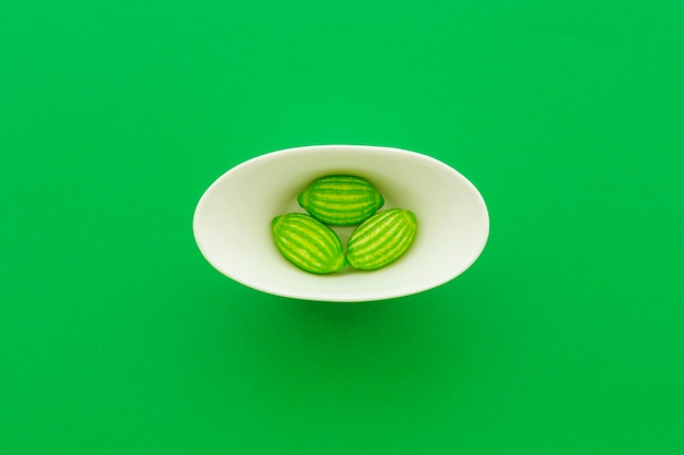 Wysokiego kąta widok cukierki w pucharze na zielonym tle