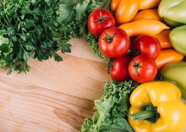 Wysokiego kąta widok kolorowi świezi warzywa na drewnianym tle