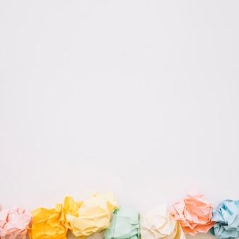 Wysokiego kąta widok kolorowi zmięci papiery na białym tle