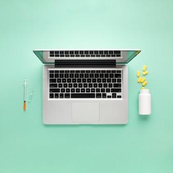 Wysokiego kąta widok laptop między zastrzykiem i strzykawką nad zieleni powierzchnią