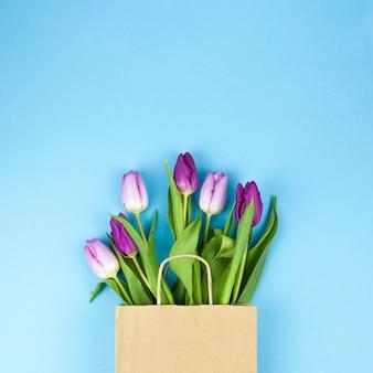 Wysokiego kąta widok purpurowi tulipanowi kwiaty na brown torbie przeciw błękitnemu tłu