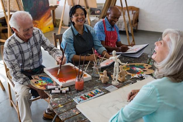 Wysokiego kąta widok rozochoceni starsi przyjaciele maluje na kanwie