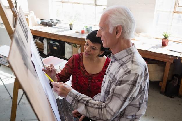 Wysokiego kąta widok starsi przyjaciele maluje na papierze