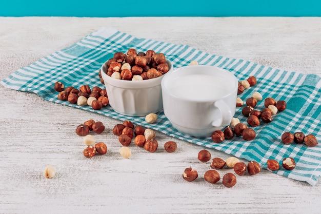 Wysokiego kąta widoku filiżanka mleko z pucharem hazelnuts na białym drewnianym i błękitnym sukiennym tle. poziomy
