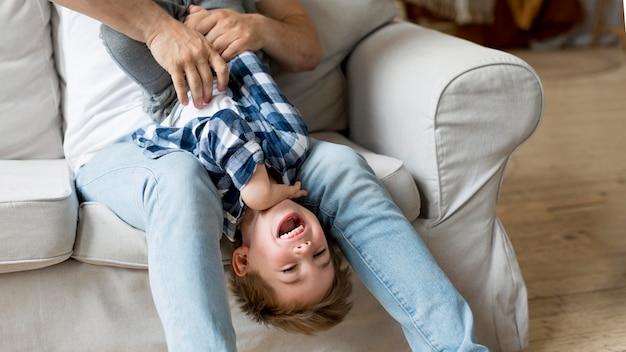 Wysokiego widoku ojciec łaskocze szczęśliwego dziecka