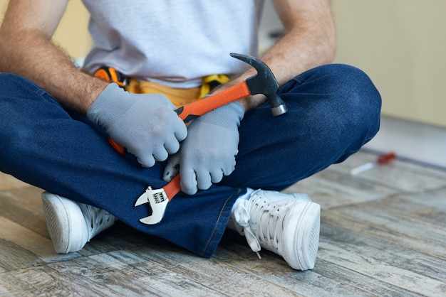 Wysokiej jakości naprawa przycięte zdjęcie młodego mechanika trzymającego w ręku młotek i klucz nastawny