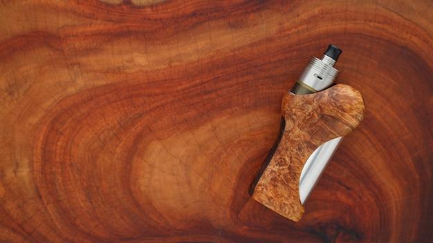 Wysokiej klasy tytanowy atomizer genesis ze stabilizowanymi modami regulowanymi z naturalnego czarnego drewna jesionowego na tle tekstury naturalnego drewna, urządzenie vaping, selektywna ostrość