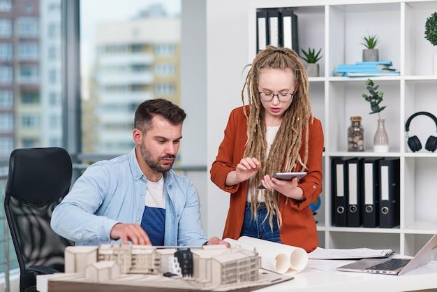 Wysoko wykwalifikowani, pracowici, kreatywni projektanci płci męskiej i żeńskiej pracujący z makietami przyszłych budynków