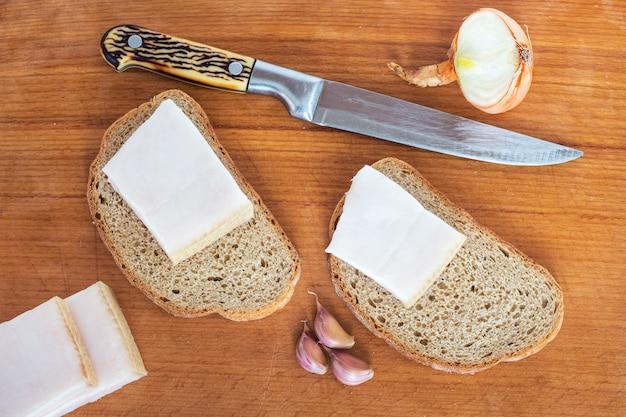Wysokokaloryczne i pożywne jedzenie przywracające siłę: chleb, tłuszcz, cebula i czosnek