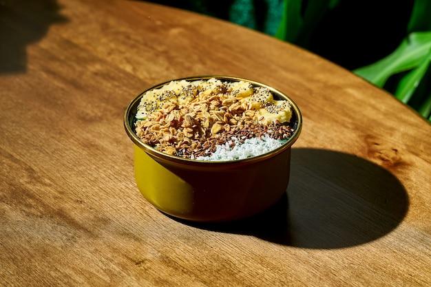 Wysokokaloryczne i zdrowe śniadanie - miska na mleku z granolą, bananem, kokosem na drewnianym tle