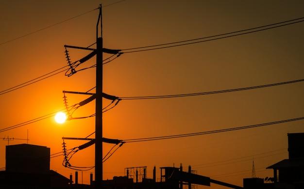 Wysokonapięciowy słup elektryczny i linie przesyłowe w mieście. słupy elektryczne o zachodzie słońca. moc i energia oszczędzanie energii. wieża wysokiego napięcia z kablem drutowym na stacji rozdzielczej.