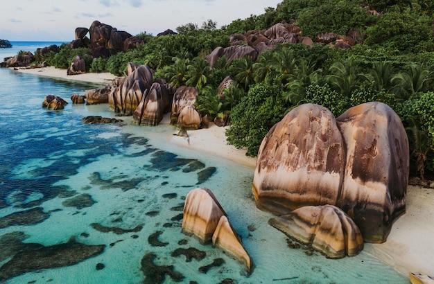 """Wyspa """"la digue"""" na seszelach. srebrna plaża z granitowym kamieniem i dżunglą. mężczyzna cieszy się wakacje i relaksuje na plaży. widok z lotu ptaka"""