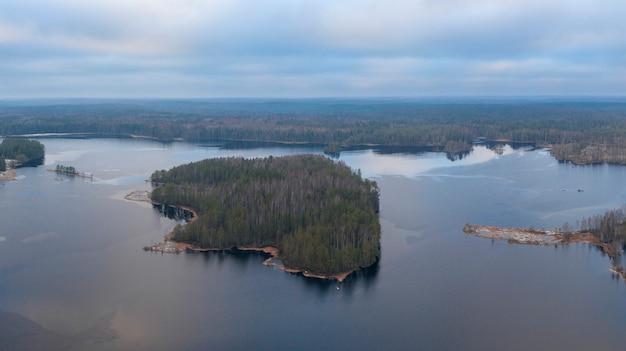 Wyspa na jeziorze miednoje wśród dużego północnego lasu w jesiennej fotografii lotniczej z drona