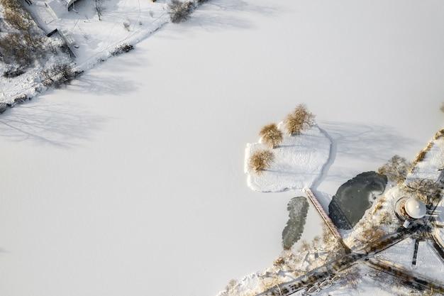 Wyspa na jeziorze z mostem w winter loshitsky park mińsk, białoruś