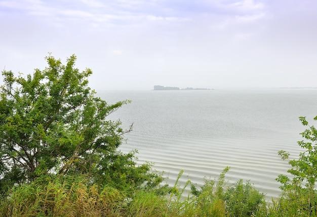 Wyspa na morzu ob brzeg zbiornika nowosybirsk w porannej mgle pod błękitnym niebem