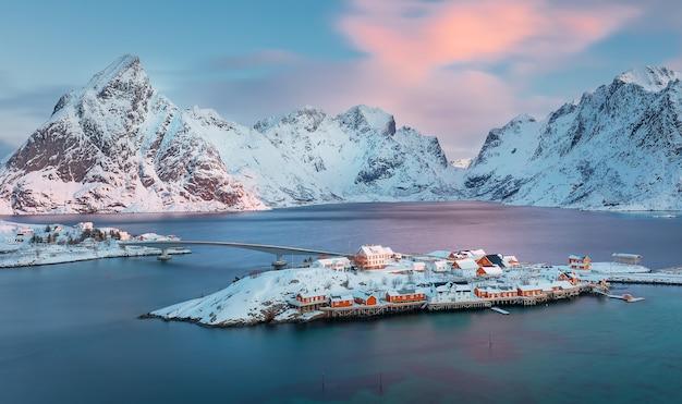 Wyspa sakrisya z pasmem górskim na tle o wschodzie słońca na lofotach w norwegii