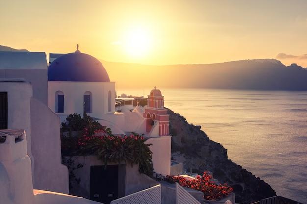 Wyspa santorini w grecji, lokalny kościół w wiosce oia na zachodzie słońca