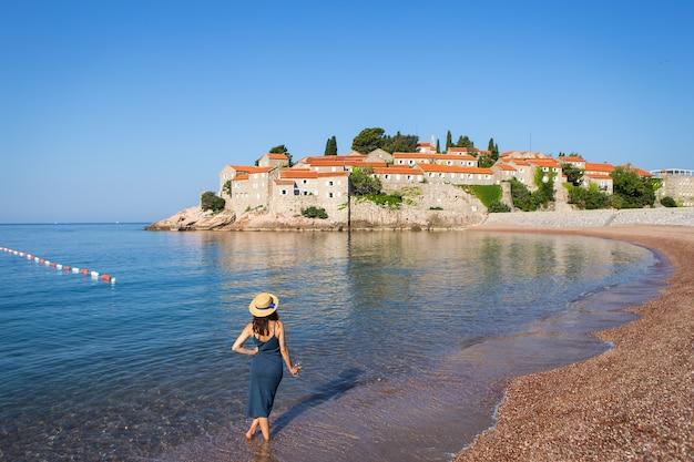 Wyspa sveti stefan, czarnogóra 5 lipca 2021: morze adriatyckie. dziewczyna w słomkowym kapeluszu stoi z lampką wina na tle wyspy świętego szczepana.