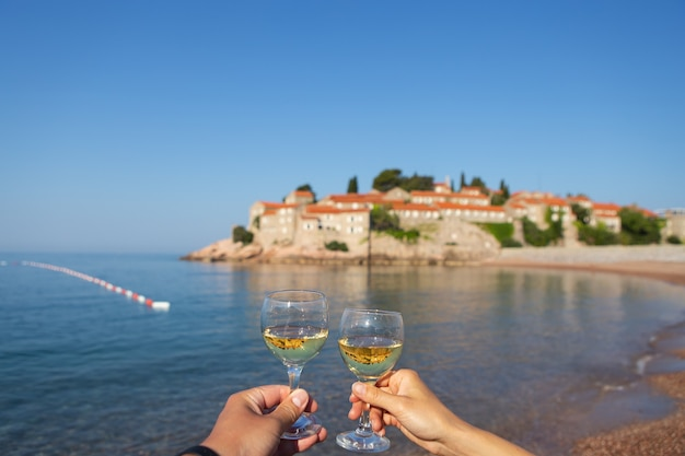 Wyspa sveti stefan, czarnogóra 5 lipca 2021: morze adriatyckie. kieliszki z winem na tle wyspy. romantyczna podróż.