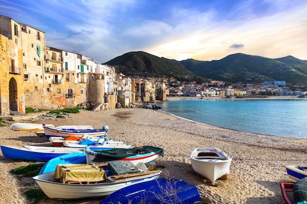 Wyspa sycylia, stare miasto cefalu z łodziami rybackimi na plaży. włochy