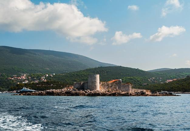Wyspa z dawną austriacką twierdzą arza. wyspa mamula. w tle widać pasmo górskie, zatokę kotorską, morze adriatyckie. widok z bliska od morza z jachtu.