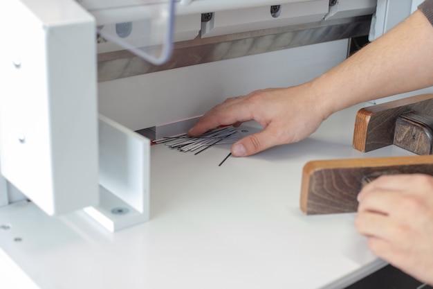 Wyspecjalizowany operator usuwa skrawki i krawędzie stosu wizytówek lub metek na automatycznej maszynie do cięcia papieru profesjonalny sprzęt do cięcia dla drukarni lub warsztatu