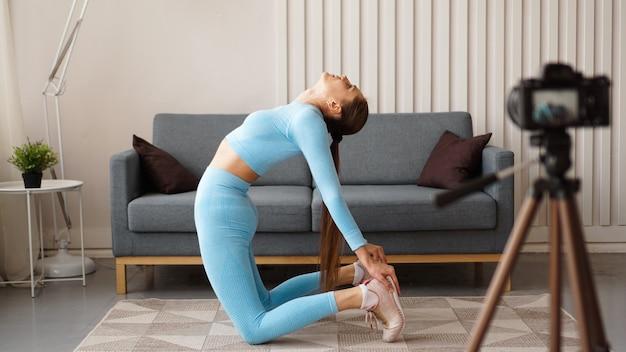 Wysportowana blogerka w odzieży sportowej kręci wideo kamerą w domu w salonie. pojęcie sportu i rekreacji. zdrowy tryb życia.