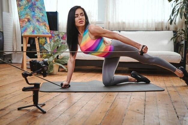 Wysportowana blogerka w średnim wieku, ubrana w różnokolorową koszulę i sportowe pozy przed kamerą, ćwiczy w domu z taśmami oporowymi.