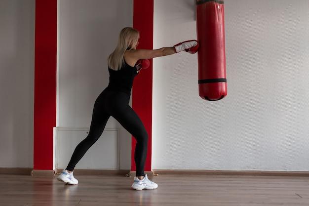 Wysportowana blondynka młoda kobieta w czarnej koszulce w czarnych legginsach sportowych w trampkach w czerwonych rękawicach bokserskich stoi i bije w worek treningowy na siłowni