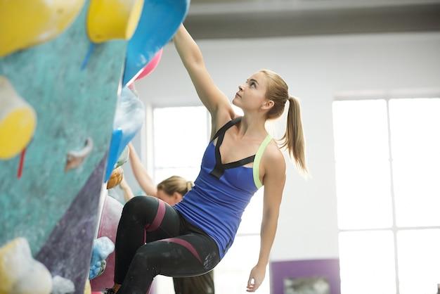 Wysportowana blondynka z kucykiem trzymając się jednej z małych skał na ściance wspinaczkowej podczas uprawiania sportów ekstremalnych na siłowni