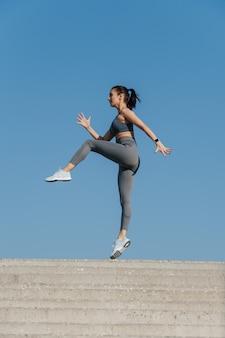 Wysportowana brunetka ćwicząca na świeżym powietrzu pod błękitnym, czystym niebem