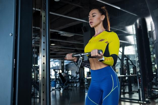 Wysportowana brunetka robi ćwiczenia bicepsa na skrzyżowaniu kabli na siłowni