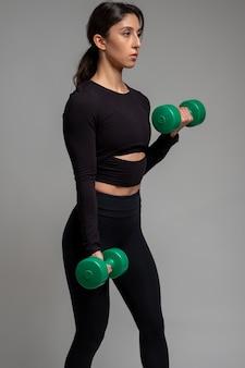 Wysportowana brunetka robi hantle biceps na szarej powierzchni